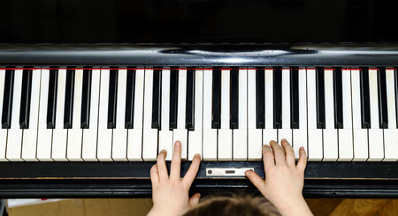 Girls hands and piano keyboard close-up view, education concept