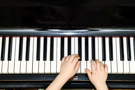 grand kid: Girls hands and piano keyboard close-up view, education concept