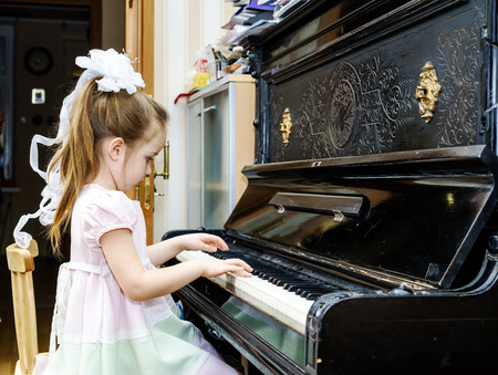 Cute little girl playing old piano at home lesson