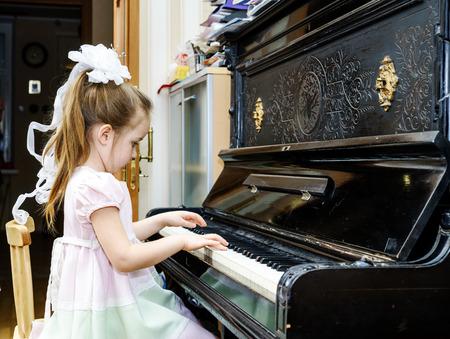 tocando piano: Ni�a linda que juega el piano de edad en casa la lecci�n Foto de archivo