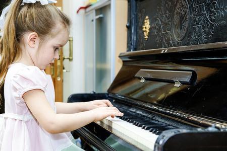 tocando el piano: Niña linda que juega el piano de edad en casa la lección Foto de archivo
