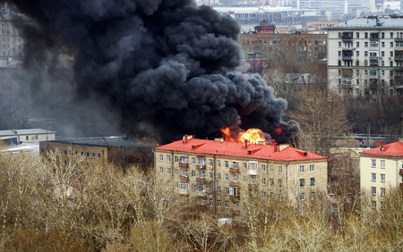 conflagration: Column of black smoke rising above fireplace in Moscow, Russia