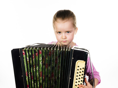 music education: Cute little girl playing harmonica, isolated on white, music education concept
