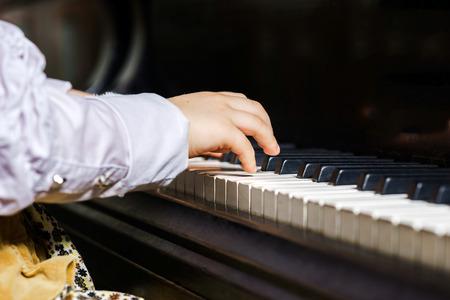 piano de cola: Ni�a linda que juega piano en la escuela de m�sica, concepto de infancia