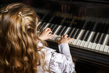 Cute little girl playing grand piano in music school, childhood concept Stockfoto