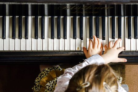 Cute little girl playing grand piano in music school, childhood concept Standard-Bild