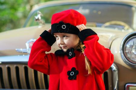 sixties: Cute little girl dressed in retro coat posing near oldtimer car, sixties