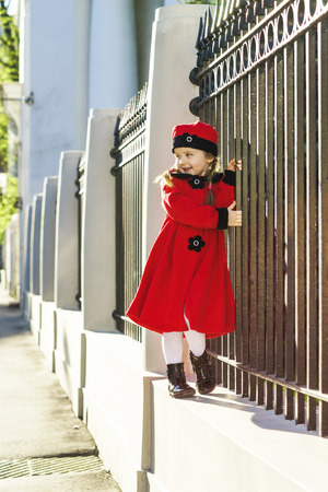 street life: Cute little girl dressed in old-style coat posing on the street, sunny day