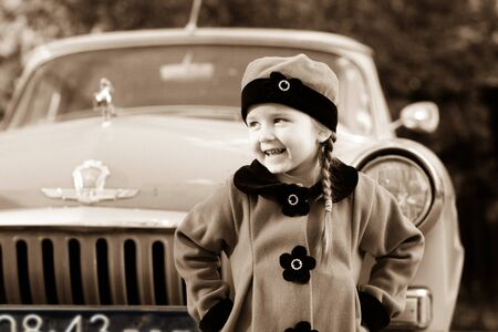 Cute little girl dressed in retro coat posing near oldtimer car, sixties