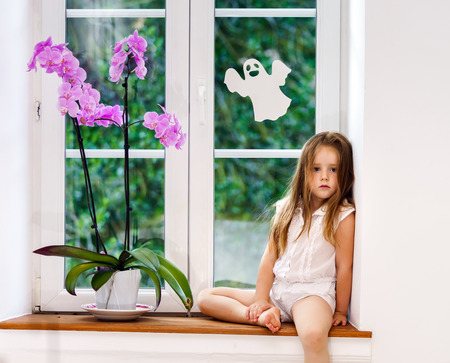 Cute little girl with flower sitting on windowsill, children safety concept Stock Photo