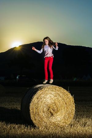 hayrick: Teenage girl jumping from the haystack, sunset