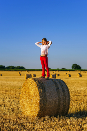 hayrick: Teenage girl with long hair posing in summer field, countryside, Alsace, France Stock Photo