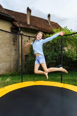 Cute teenage girl jumping on trampoline, childhood concept Reklamní fotografie - 43761685