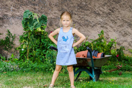 helpmate: Cute little girl helping her mother in the backyard with heavy wheelbarrow Stock Photo