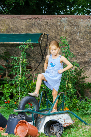 garden staff: Cute little girl helping her mother in the backyard with heavy wheelbarrow Stock Photo
