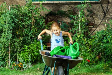 helpmate: Cute little girl gardening in the backyard. Childhood concept.