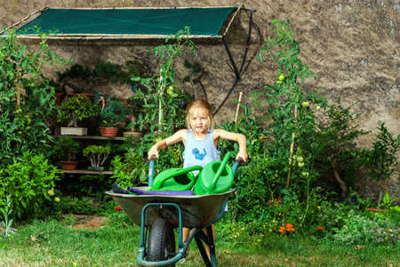 garden staff: Cute little girl gardening in the backyard. Childhood concept.