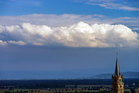 belltower: Beautiful big cloud over the belltower of old church, France