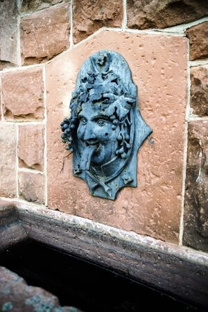bacchus: Funny bas-relief of Bacchus head as part of the fountain, France, Alsace Stock Photo