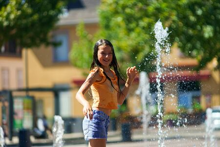 hot day: Two sisters playing with fountain splash on the central street of Selestat