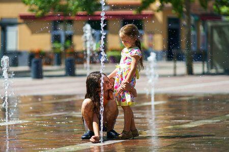 两姐妹在Selestat中心大街上玩喷泉水花