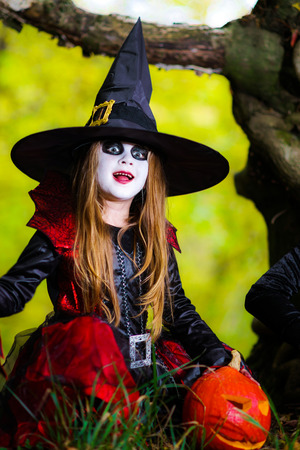 woodland  horror: Cute girl dressed to Halloween costume in dark forest, holiday concept