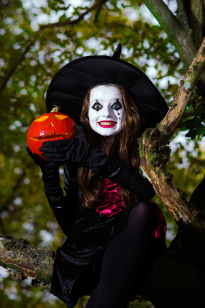woodland  horror: Teenage girl dressed in witch costume sitting on the tree, Halloween concept