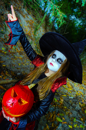 woodland  horror: Little girl dressed in witch costume in Halloween forest with pumpkin