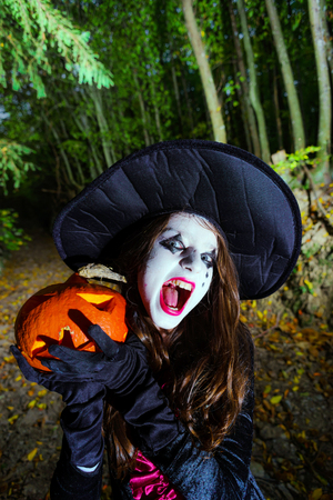 woodland  horror: Teenage girl with pumpkin in Halloween forest, holiday concept Stock Photo