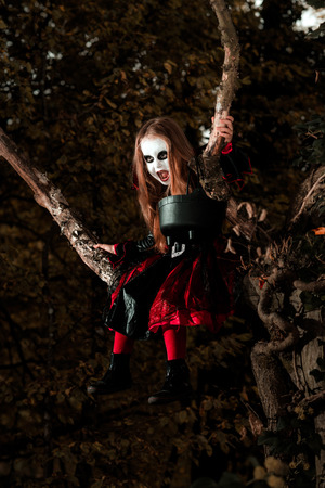 woodland  horror: Cute little girl dressed in Halloween costume sitting on the tree like a witch Stock Photo