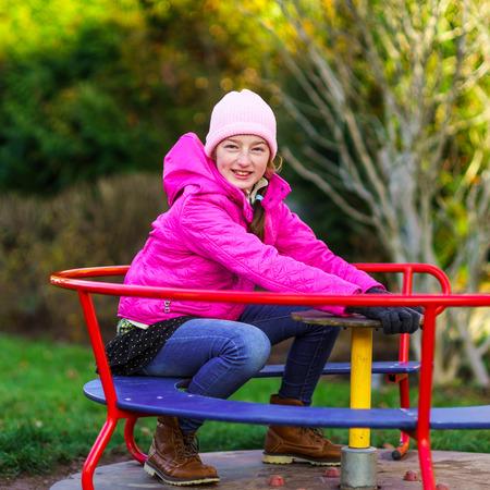 turnaround: Teenage girl on small roundabout, children playground