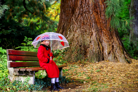 pinetree: Cute little girl with umbrella sitting under the big pinetree in national park