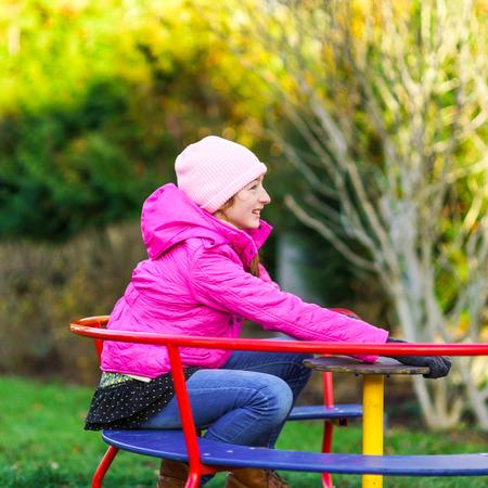 roundabout: Teenage girl on small roundabout, children playground