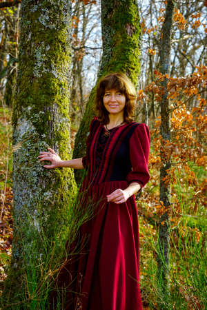 queen's theatre: Woman in red renaissance dress portrait, autumnal forest, France