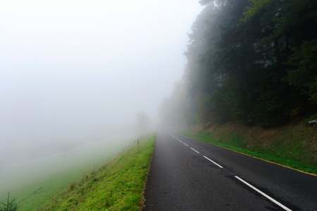 road autumnal: Danger foggy road in the forest, autumnal landscape Stock Photo
