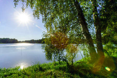 light beams: Sun with reflection in water over the lake, summer evening Stock Photo