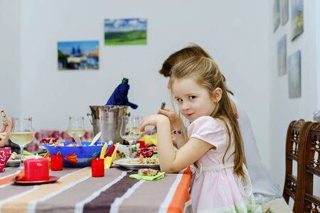 portarit: Cute little girl eating with her mother, indoor portarit Stock Photo