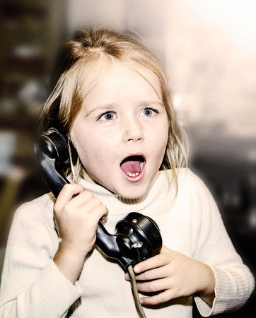 emotive: Little emotive girl speaking vintage wired telephon