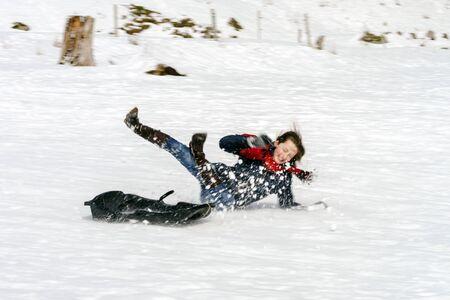 YTeenage niña que cae desde trineos, tiempo de nieve en invierno
