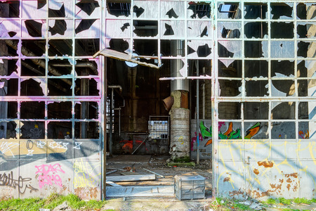 tagging: Old abandoned plant with graffity on walls, destroyed ruins Editorial