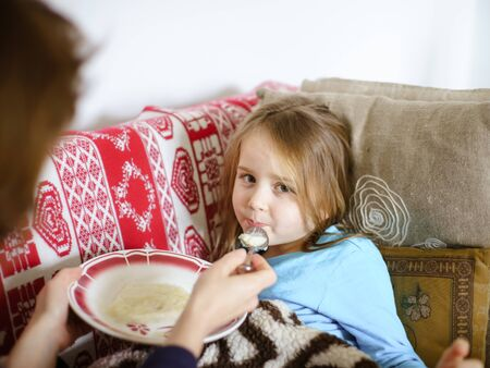 catarrh: Mother feeding taken ill daughter by semolina, spoonfeeding