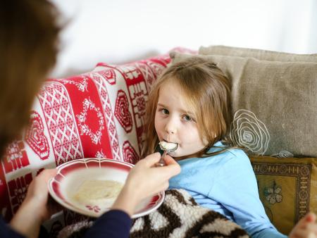 catarrh: Mother feeding taken ill daughter by semolina, spoonfeeding
