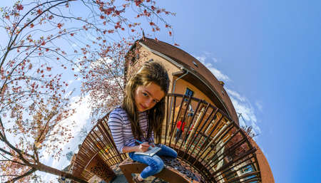 curvature: Teenage girl drawing in the park, comic view with space curvature, little planet Stock Photo
