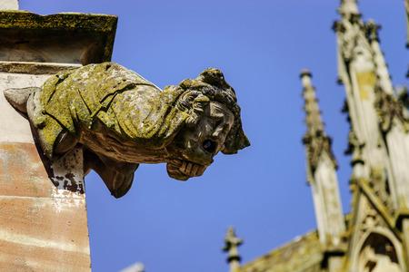 Gargoyle on a gothic cathedral, detail of a tower on blue sky background, Saint Florent church, Niederhaslach, France