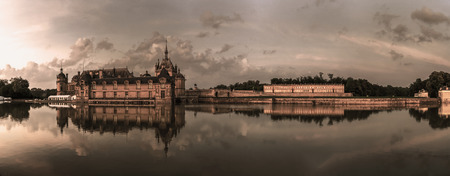 chantilly: Chantilly castle panoramic view on sunset background with reflection in the water