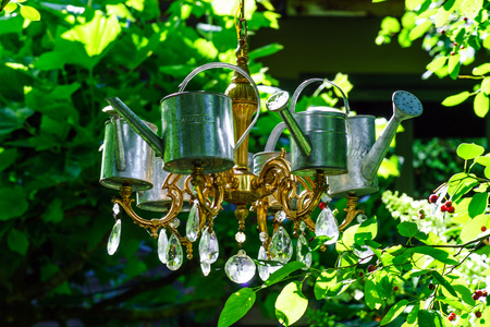 luster: Decorative luster in the summer garden, watering pots and chandellier Stock Photo