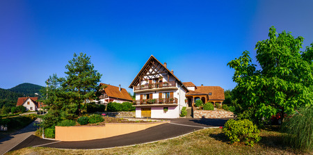 guesthouse: Beautiful guesthouse in Alsace, France. Alpine style decoration. Sunny day, vibrant colors.