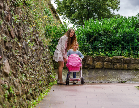 play the old park: Two sisters with babycarrier for dolls, outdoor. Childhood concept