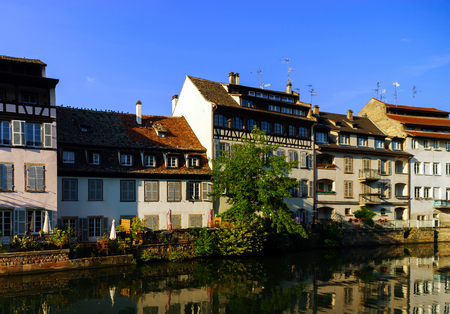 old center: Old center of Strasbourg. Typical alsacien houses on the river. Vivid colors on sunset. Touristic concept. Stock Photo