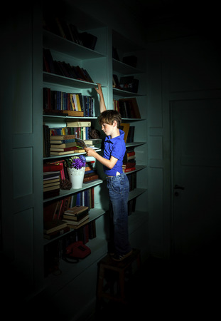 carroty: Freckled red-haired little boy searching book on bookcase in bibliotek Stock Photo